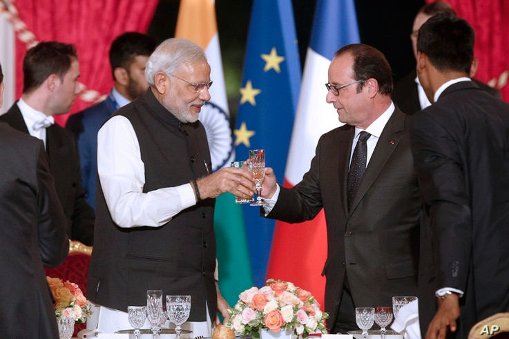 FILE - French president Francois Hollande, right, toasts with Indian Prime Minister Narendra Modi during an official dinner at the Elysee Palace in Paris, France, 10 April 2015.
