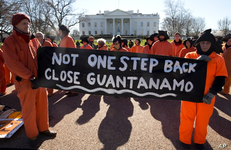 """Protesters wearing orange jumpsuits depicting Guantanamo Bay detainees, hold a sign that reads """"Not One Step Back Close Guantanamo"""" participate in a rally outside of the White House in Washington Monday, Jan. 11, 2016, calling for a close of the dete..."""