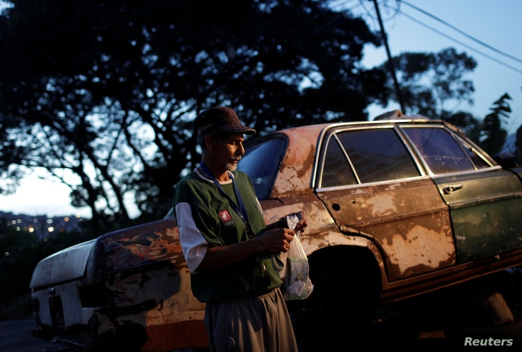 """Eduardo Liendo, 63, who lives inside an old car, holds his prize money which he won on """"Los Animalitos"""" (or the Little Animals) betting game on the outskirts of Caracas, Venezuela, October 11, 2017."""