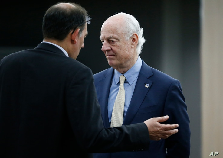 U.N. mediator Staffan de Mistura, right, listens to a member of his staff before a meeting with the Syrian government delegation during Syria Peace talks at the United Nations in Geneva, Switzerland, April 26, 2016.