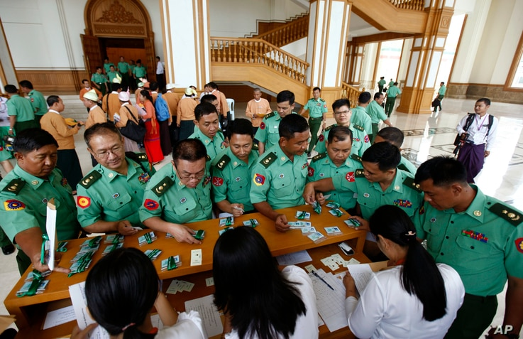 Appointed lawmakers who represent Myanmar's military mark their attendance for a regular session of lower house of Parliament Monday, July 25, 2016 in Naypyitaw, Myanmar.