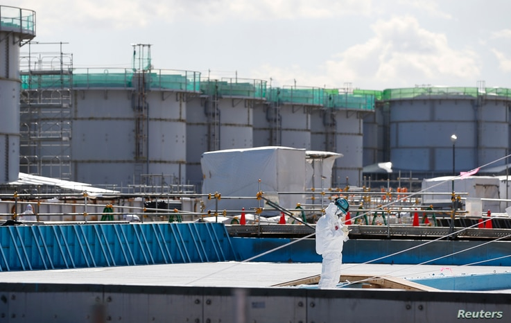 A worker, wearing protective suits and masks, takes notes in front of storage tanks for radioactive water at Tokyo Electric Power Co's (TEPCO) tsunami-crippled Fukushima Daiichi nuclear power plant in Okuma town, Fukushima prefecture, Japan, Feb.10,