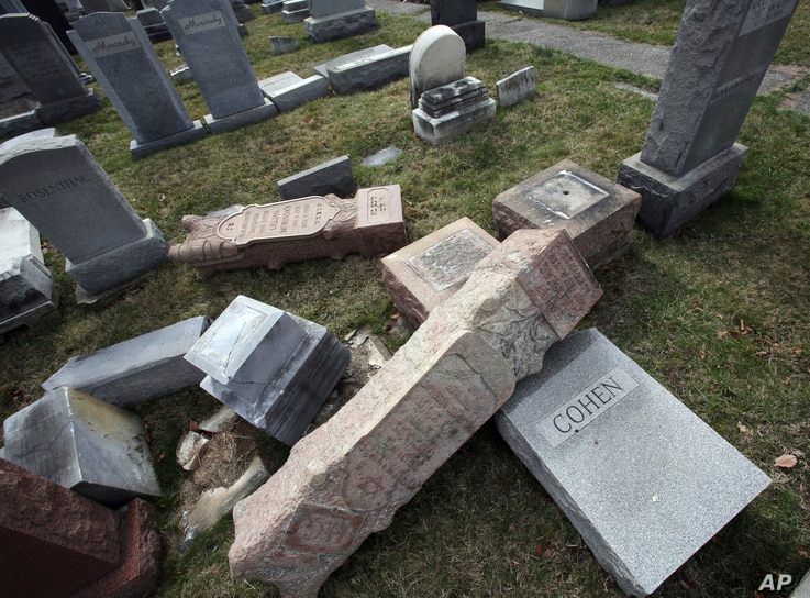 Damaged headstones rest on the ground at Mount Carmel Cemetery, Feb. 27, 2017, in Philadelphia. More than 100 headstones have been vandalized at the Jewish cemetery in Philadelphia.