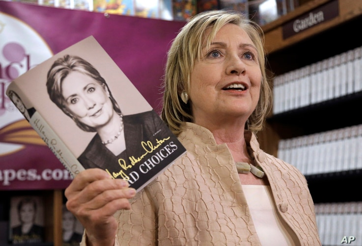"""Former Secretary of State Hillary Rodham Clinton holds her memoir """"Hard Choices"""" at Bunch of Grapes Bookstore, in Vineyard Haven, Massachusetts, on the island of Martha's Vineyard, Aug. 13, 2014, during a book signing event for her memoir """"Hard Choic..."""