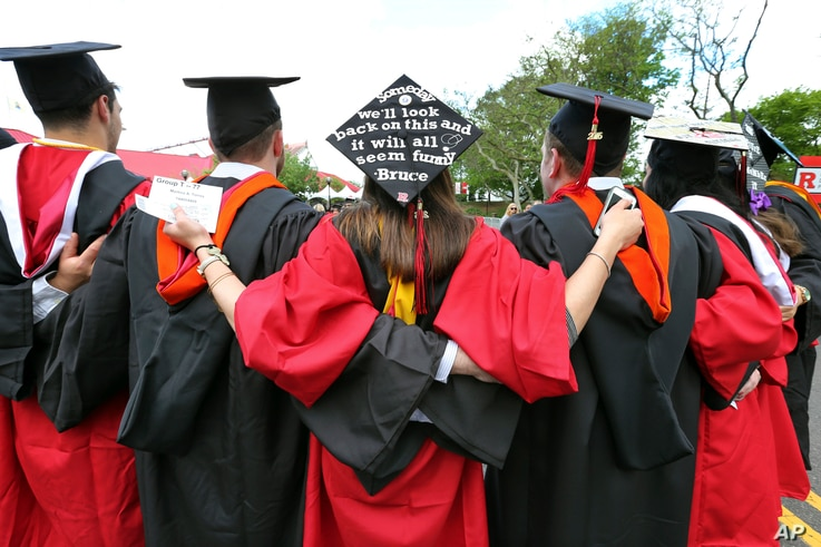 FILE - In this May 15, 2016, photo, students embrace as they arrive for the Rutgers graduation ceremonies in Piscataway, N.J.  More Americans are getting buried by student debt, causing delays in home ownership, limiting how much people can save and ...