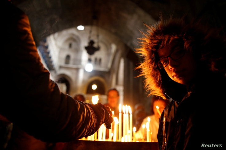 Worshippers light candles inside the Church of the Holy Sepulcher in Jerusalem's Old City, Dec. 24, 2017.