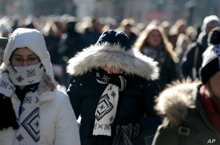 Pedestrians try to keep warm while walking in New York's Times Square, Dec. 27, 2017. Freezing temperatures and below-zero wind chills socked much of the northern United States, and the snow-hardened city of Erie, Pa., dug out from a record snowfall....