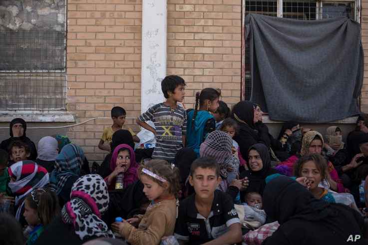Women and children from Hawija sit outside a Kurdish screening center in Dibis, Iraq, Oct. 3, 2017. Some men, after being separated from the women and children, are investigated for involvement in the Islamic State group.