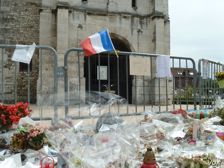 Offerings are left outside St. Etienne Church, where Father Jacques Hamel was killed while celebrating Mass in July. (L. Ramirez/VOA)