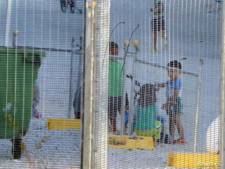 FILE - An undated supplied image from Amnesty International claiming to show children playing near a fence at the country's Australian-run detention centre on the Pacific island nation of Nauru.