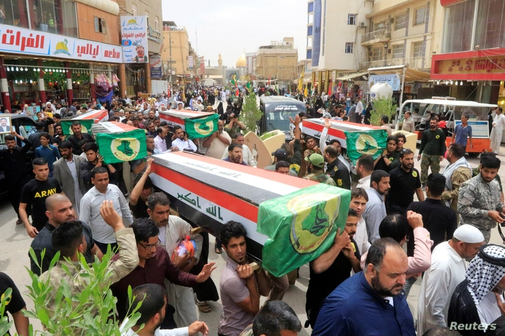 Mourners carry the coffins of fighters from Iraqi paramilitary troops who were killed in a battle against the Islamic State in the ancient city of Hatra, south of Mosul, during the funeral in Najaf, Iraq, April 27, 2017.