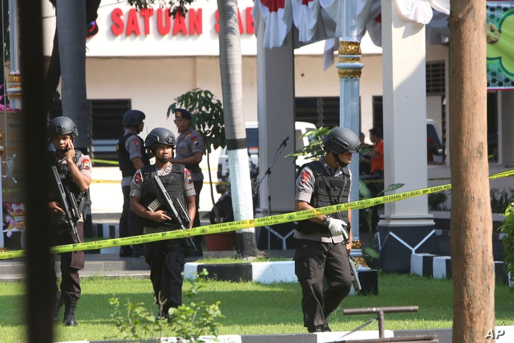 FILE - Members of a police bomb squad examine the area where a suicide bomber blew himself up at the local police headquarters in Solo, Central Java, Indonesia, July 5, 2016. Police said the bomber was a friend of Bahrun Naim, one of the hundreds of ...