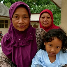 Ibu Parmi sits with friends at Kapuharjo evacuation shelter in Indonesia.