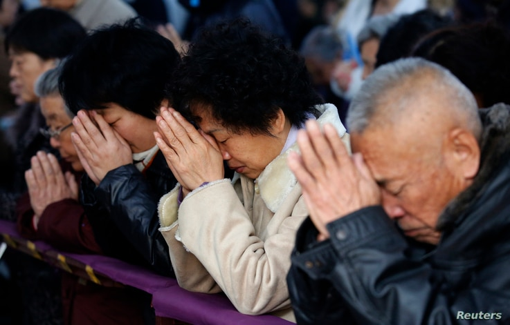 FILE - Believers take part in a weekend mass at an underground Catholic church in Tianjin.