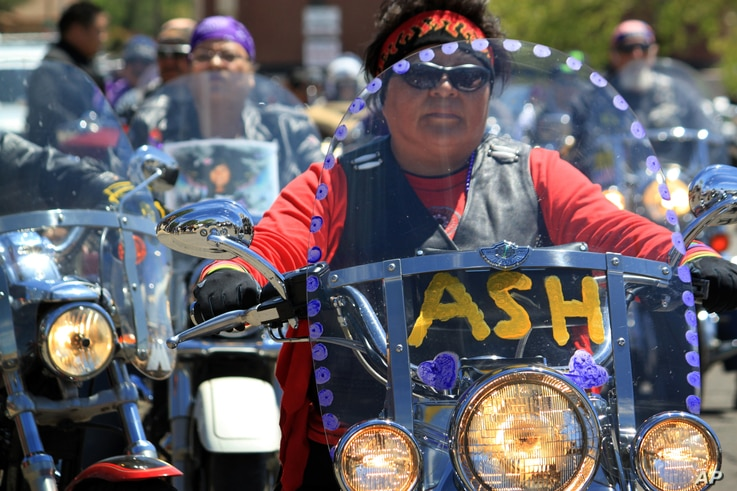 Regina Mike, right, decorated the windshield of her motorcycle in honor of her relative, 11-year-old Ashlynne Mike, as she and hundreds of other motorcyclists escorted the girl's casket following a memorial service in Farmington, N.M., May 6, 2016.