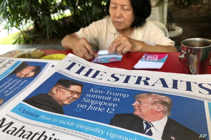 A news vendor counts her money near a stack of newspapers with a photo of U.S. President Donald Trump, right, and North Korea's leader Kim Jong Un on its front page on May 11, 2018, in Singapore.