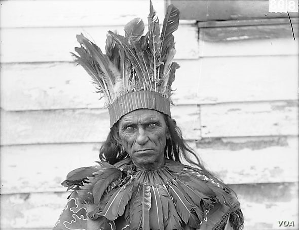 William Terrill Bradby, a Pamunkey Indian, in traditional dress and holding a club, sits for a portrait by the photographer De Lancey W. Gill in October 1899. BAE GN 00893 06197600, National Anthropological Archives, Smithsonian Institution