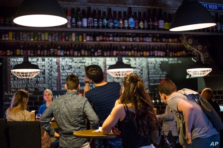 In this July 21, 2017 photo, people review the craft beer choices at the RULE Taproom pub.