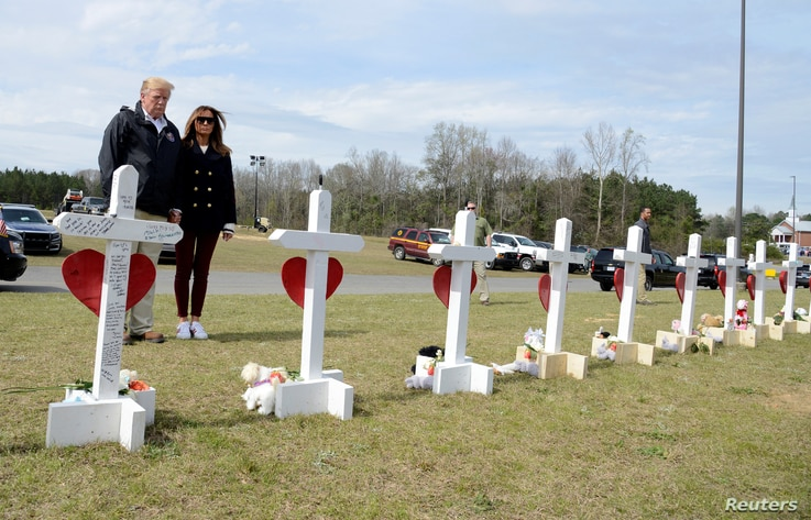 U.S. President Donald Trump and first lady Melania Trump pause at a row of crosses for the victims of a tornado in Beauregard, Alabama, March 8, 2019.