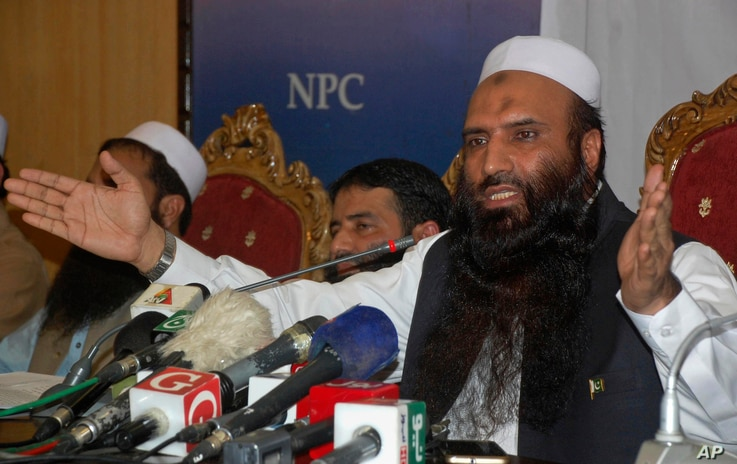 Saifullah Khalid, right, a longtime official of the banned militant Jamaat-ud-Dawa group, and president of the newly-formed Milli Muslim League party, addresses a news conference in Islamabad, Aug. 7, 2017.