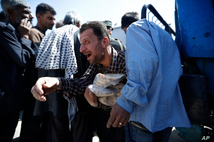 A Syrian man holds bread as Syrian authorities distributed bread, vegetables and pasta to Douma residents, in the town of Douma, Syria, Monday, April 16, 2018.