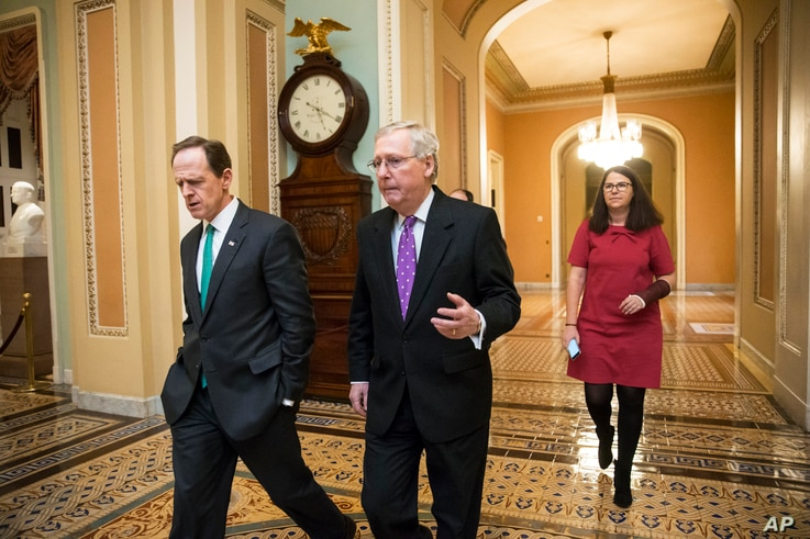 Senate Majority Leader Mitch McConnell, center, walks with Sen. Pat Toomey to the chamber for the vote to impose more stringent sanctions on North Korea, Feb 10, 2016.