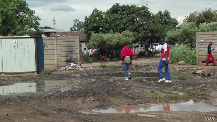 Residents of Mbare township - the navigates through raw sewerage one of the causes of typhoid, a water borne disease which Zimbabwean authorities are battling to end since the beginning of the rain season about two months ago, Harare, Zimbabwe, Jan. ...