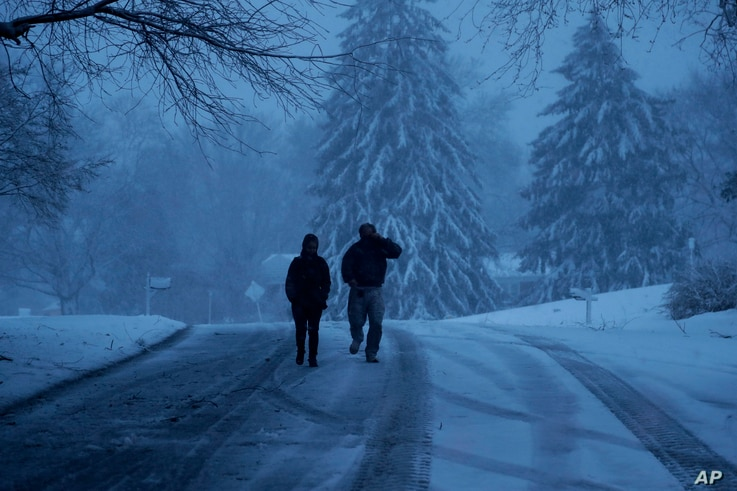 A family walks down a snowy street during a winter storm, March 2, 2018, in Marple Township, Pa.