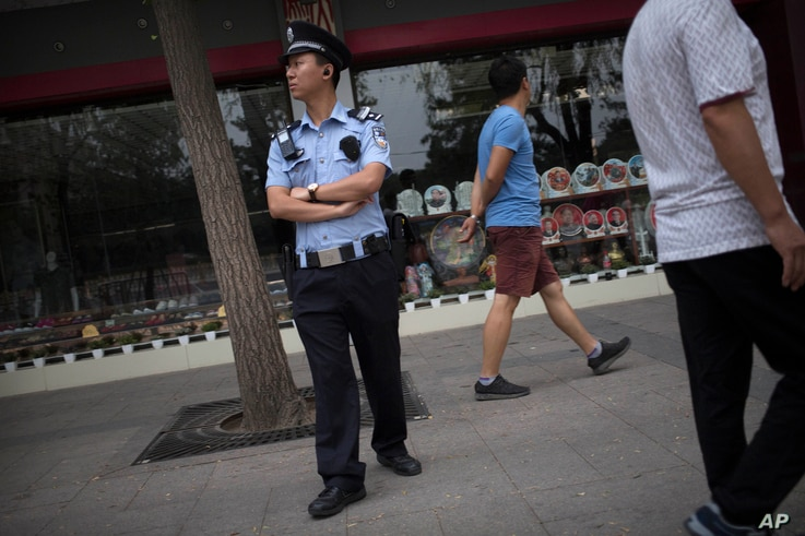 A police officer stands guard on the sidewalk of a street adjacent to Tiananmen Square in Beijing, June 4, 2016. The day marked the 27th anniversary of China's bloody crackdown on pro-democracy protests which centered on the square.