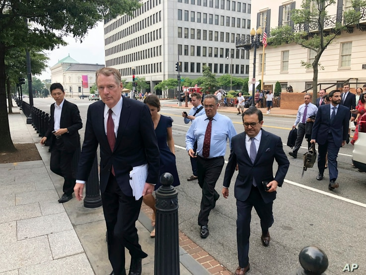 United States Trade Representative Robert Lighthizer, front left, and Mexican Secretary of Economy Idelfonso Guajardo, front right, walk to the White House, Aug. 27, 2018.
