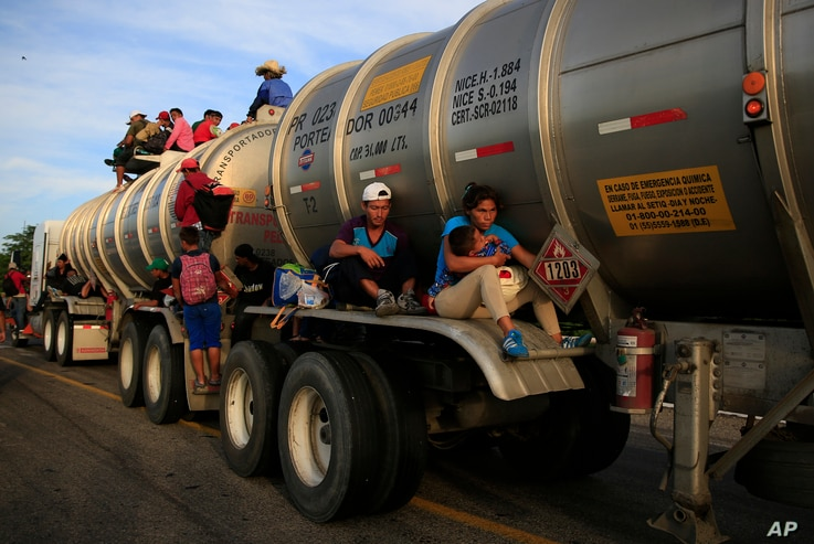A woman holding her baby hitches a ride on the fender of a tanker in Niltepec, Mexico, Oct. 30, 2018.