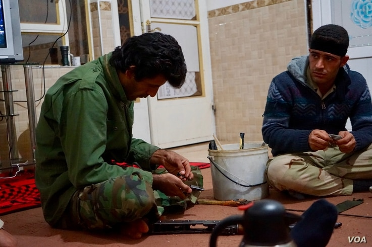 A peshmerga fighter sets about fixing a 30-year-old AK-47 hours before a battle with Islamic State militants, Nov. 6, 2016. (J. Dettmer/VOA)