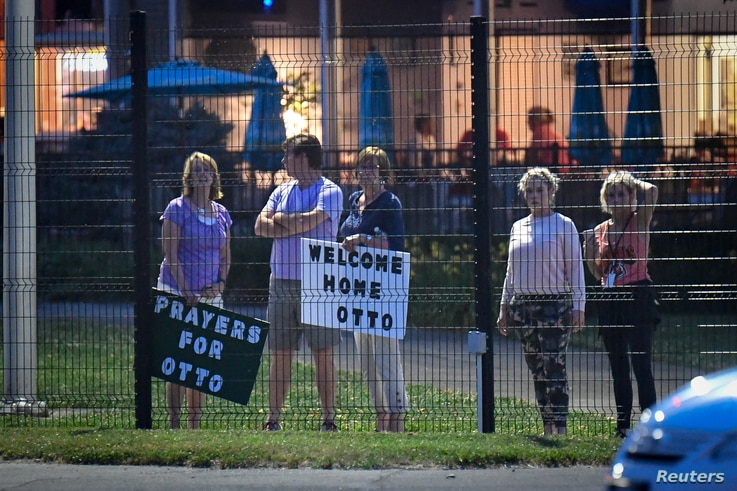 Local residents hold signs of support to welcome home Otto Warmbier at Lunken Airport in Cincinnati, Ohio, June 13, 2017.