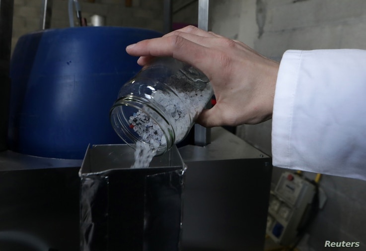 Christofer Costes, a French inventor who created a machine that turns plastic waste into fuel pours pieces of plastic in his invention in Puget-Theniers, France, Dec. 14, 2018.