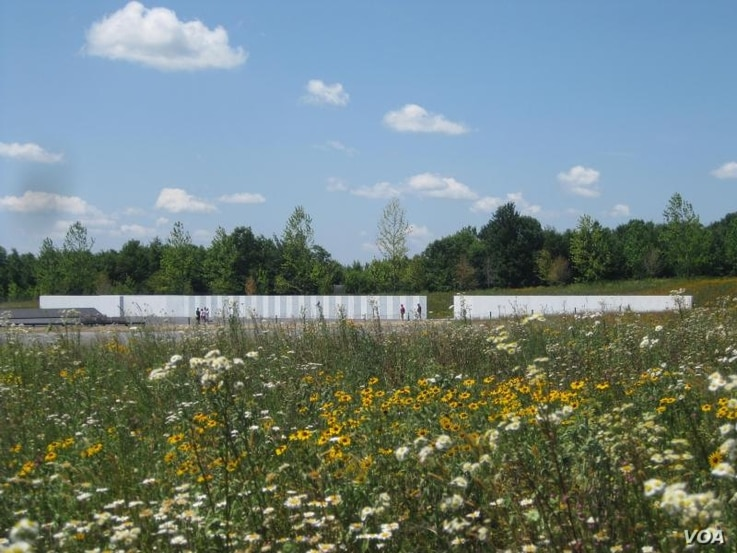 A wildflower meadow sweeps down from the Ring Road to the edge of the Wall of Names at the Memorial Plaza.