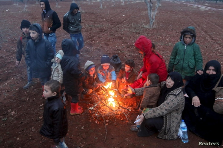 FILE - Displaced people, who fled the violence in northern Syria, huddle around a fire in the Syrian village of Akda hoping to cross into Turkey, Jan. 23, 2016. Turkey's border guards prevented the displaced people from approaching the border, activi...