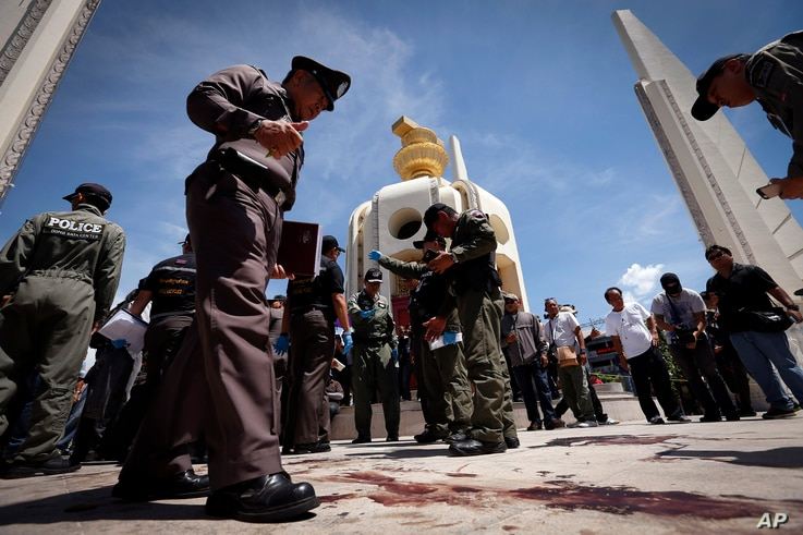 Thai police investigate following an overnight shooting attack at Democracy Monument in Bangkok, Thailand, Thursday, May 15, 2014. Explosions and an overnight shooting attack on opposition demonstrators in Thailand's capital killed at least two peopl...