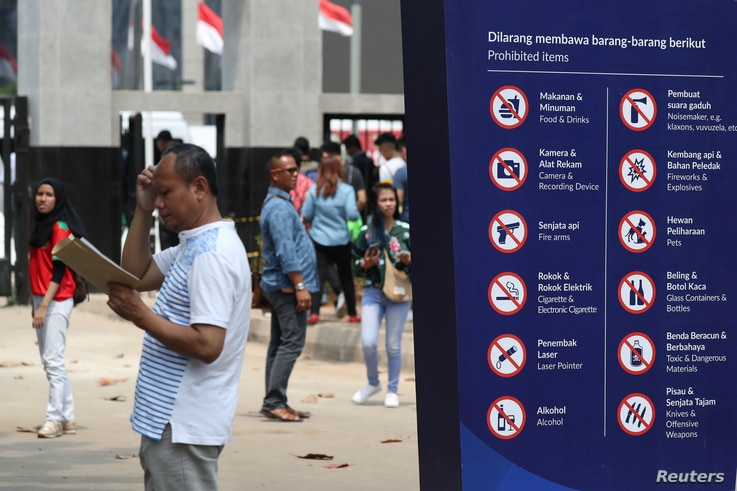 A man stands next to a sign showing prohibited items at a gate of the Gelora Bung Karno sports complex, ahead of the 2018 Asian Games in Jakarta, Indonesia, Aug. 17, 2018.
