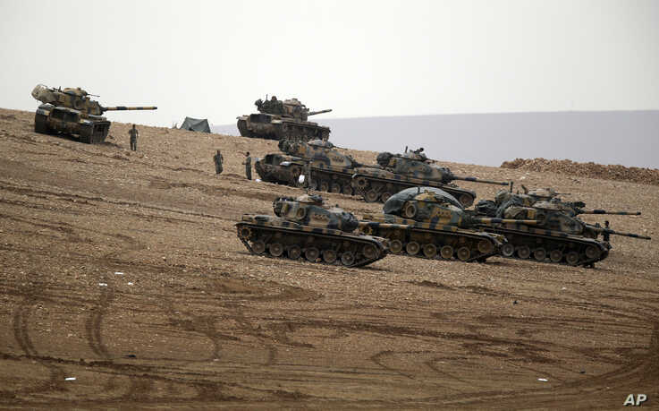 Turkish soldiers hold their positions with their tanks on a hilltop on the outskirts of Suruc, at the Turkey-Syria border, overlooking Kobani, Syria, during fighting between Syrian Kurds and the militants of Islamic State group, Oct. 12, 2014.