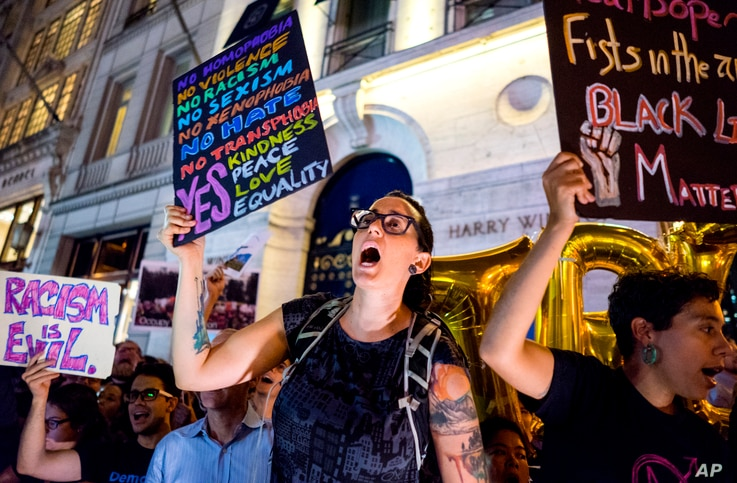 Protesters near Trump Tower react as President Donald Trump arrives, Aug. 14, 2017, in New York.