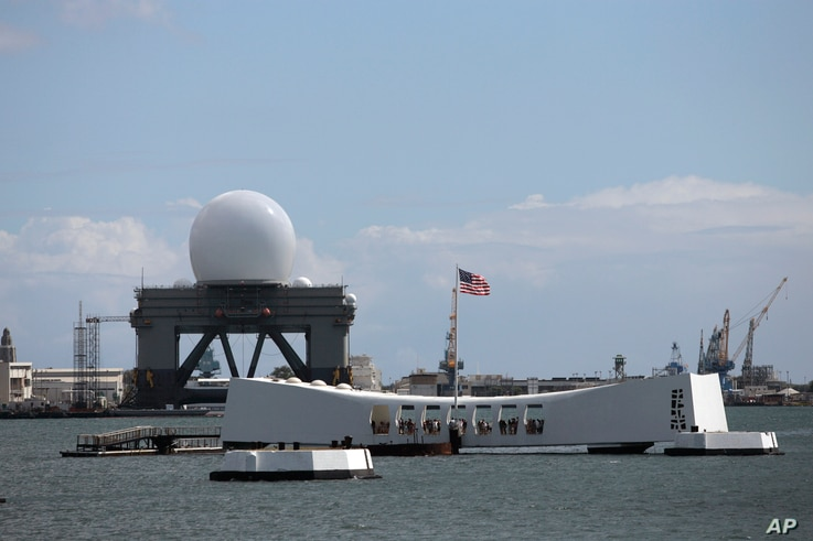 With the USS Arizona Memorial in the foreground, the Sea-Based X-band Radar (SBX) is seen, July 16, 2007 in Pearl Harbor, Hawaii.  The military's $900 million, 28-story-tall missile defense radar was back in Hawaii from its remote base in Alaska for ...