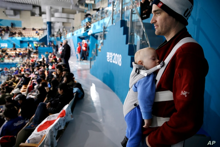 Jeff Whitmore from Wisconsin watches as his 1-year-old son, Escher, sleeps during the women's curling match at the 2018 Winter Olympics in Gangneung, South Korea, Feb. 17, 2018.