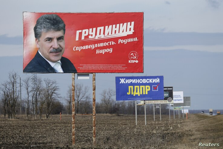 Billboards, which advertise the campaign of candidates in the upcoming presidential election for Pavel Grudinin, left, and Vladimir Zhirinovsky, second left, are on display near a road outside Stavropol, Russia, March 4, 2018.