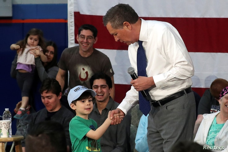 A boy wearing a Ted Cruz cap shakes hands with U.S. Republican presidential candidate John Kasich during a campaign event in Syracuse, New York, April 18, 2016.