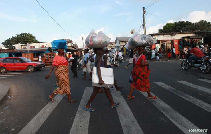 FILE - People cross a road in Monrovia. Despite hundreds of millions of dollars in foreign investment, infrastructure in Liberia remains poor.