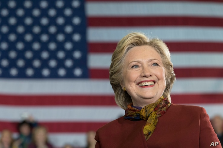 Democratic presidential candidate Hillary Clinton smiles as Democratic vice presidential candidate Sen. Tim Kaine, D-Va., speaks during a campaign event at the Taylor Allderdice High School, Oct. 22, 2016, in Pittsburgh, Pa.