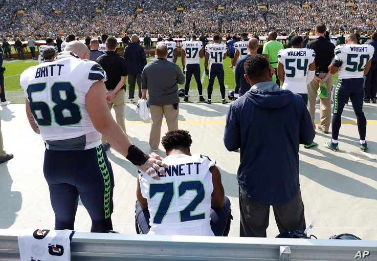 Seattle Seahawks' Michael Bennett remains seated on the bench during the national anthem before an NFL game against the Green Bay Packers, Sept. 10, 2017, in Green Bay, Wisconsin.