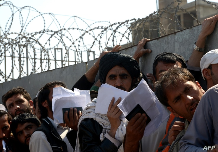 Afghan nationals carry their passports as they wait to extend their visas outside the Pakistani immigration office in Peshawar on March 13, 2017, following the Pakistani Torkham and Chaman borders were closed with Afghanistan. A spike in tensions led...
