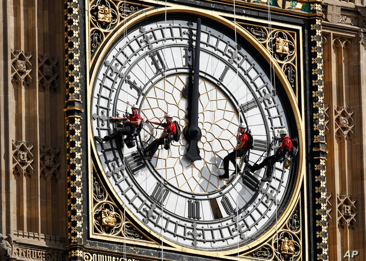 Workers hang outside the clock face as they clean the Big Ben clock tower of the Houses of Parliament in London, Monday, Aug. 18, 2014.