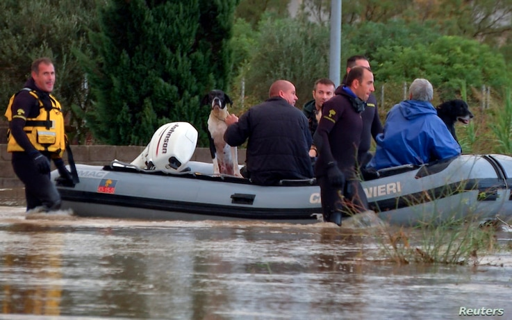 Rescue workers pulling a boat wade on a flooded street at San Gavino Monreale, Sardinia, Italy, Nov. 18, 2013.